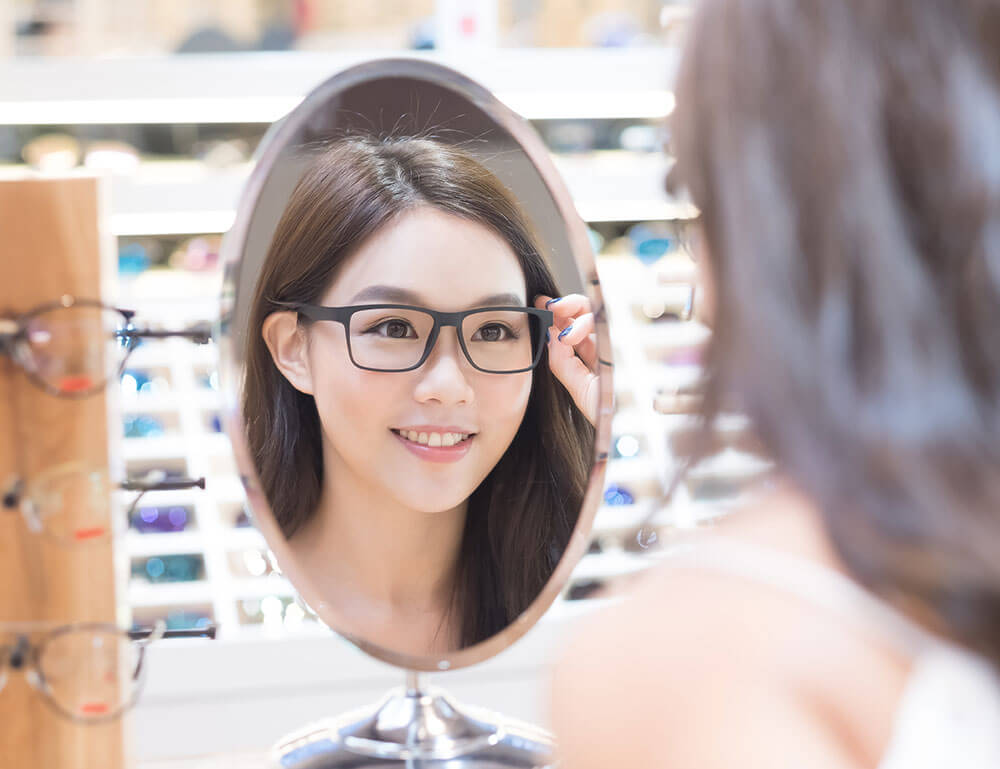 Smiling woman admiring her glasses in a mirror at optical shop