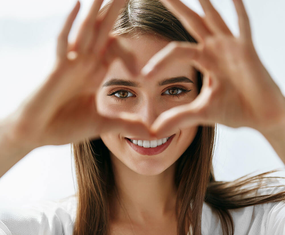 Smiling woman making a heart with her hands