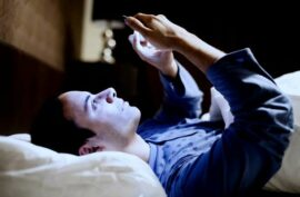 Man laying in bed looking at his phone