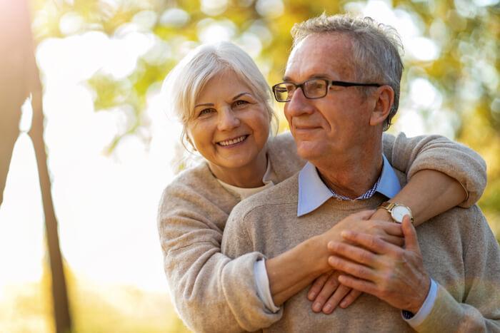 senior couple outdoors wearing beige sweaters