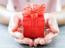 Hands holding small gift package with big red bow on top