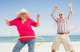 Older couple having fun on a beach with hula hoops