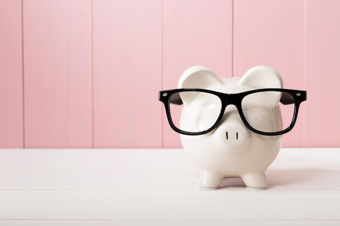 white piggy bank wearing black glasses in front of a pink wall
