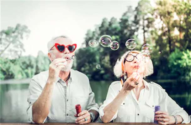 Older couple silly glasses blowing bubbles