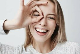 """Happy woman giving the """"ok"""" hand sign around eye"""