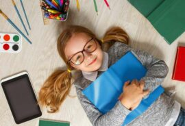 Little girl with glasses and school supplies