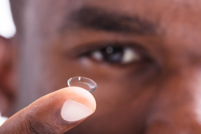 close up of contact lens on finger with face in background