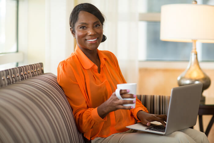 beautifule woman in orange shirt with coffee and laptop